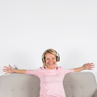 Blonde smiling portrait of a mature woman with headphone stretching her arms against white background
