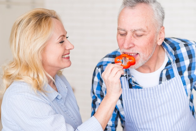 Blonde smiling senior woman feeding red bell pepper slice to his husband