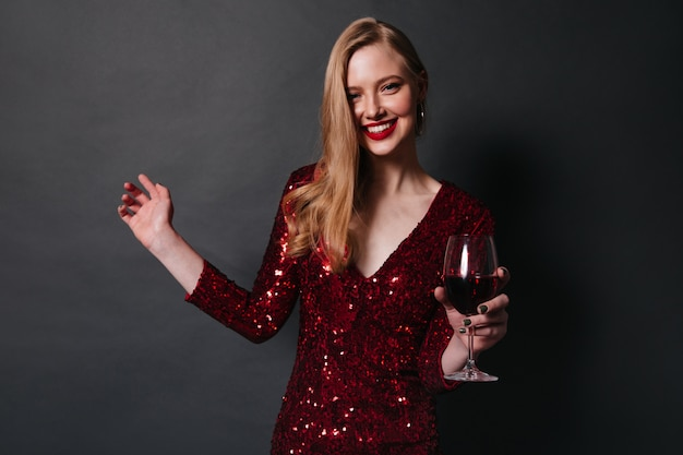 赤ワインを飲む金髪の笑顔の女性。黒の背景に踊るドレスを着たかわいい女の子のスタジオショット。