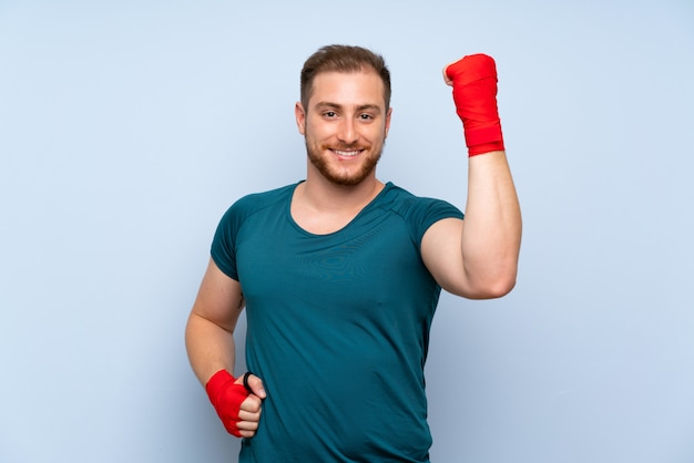 Blonde sport man over blue wall in boxing bandages