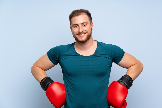 Blonde sport man over blue wall with boxing gloves
