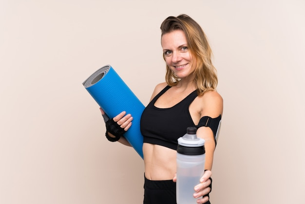 Blonde sport woman over isolated wall with sports water bottle and with a mat