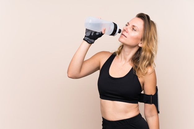 Blonde sport woman over isolated wall with sports water bottle