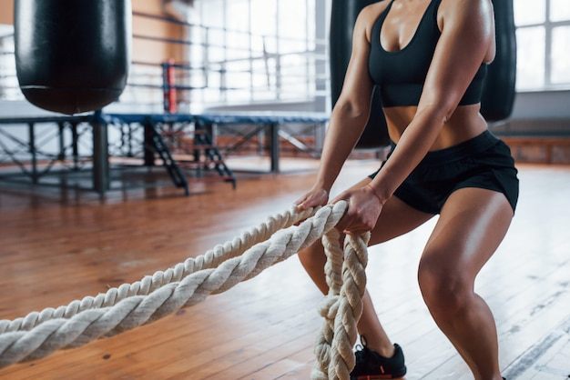 Blonde sport woman with ropes in the gym. strong female.