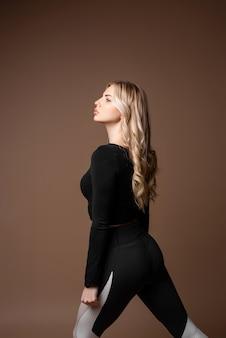 Блондинка спортивный девушка в черной спортивной одежды позирует в студии. фотография девушки с совершенным телом на бежевом фоне. сила и мотивация