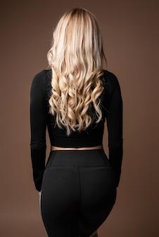 베이지색 배경에 포즈를 취하는 검은색 운동복을 입은 날씬한 그을린 몸을 가진 금발의 스포티한 여성. 배면도