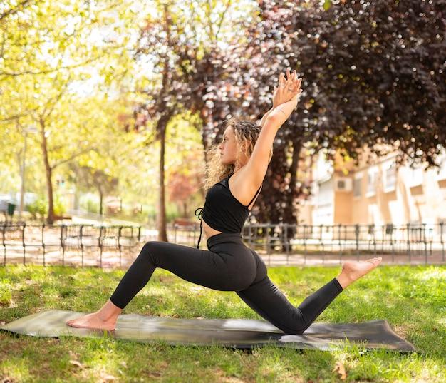 コンクリートの空間でポーズ難しいヨガを練習している金髪の強い見習い女性。