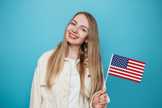 Блондинка студентка держит маленький американский флаг и улыбается на синем фоне