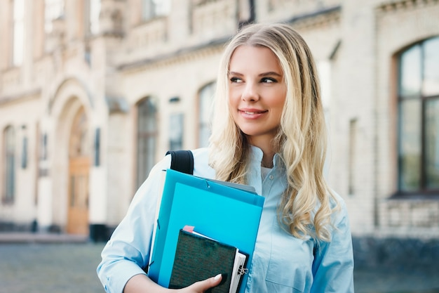 A blonde student girl is smiling and holding a folder and a notebook in her hands on a university background