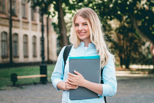 Blonde student girl is smiling and holding a folder and a notebook in her hands in university