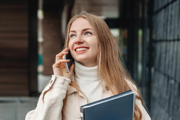 휴대 전화에 금발 학생 소녀 회담, 그녀의 손에 노트북 폴더를 보유, 미소, 대학 건물에 대 한 측면에 보인다.