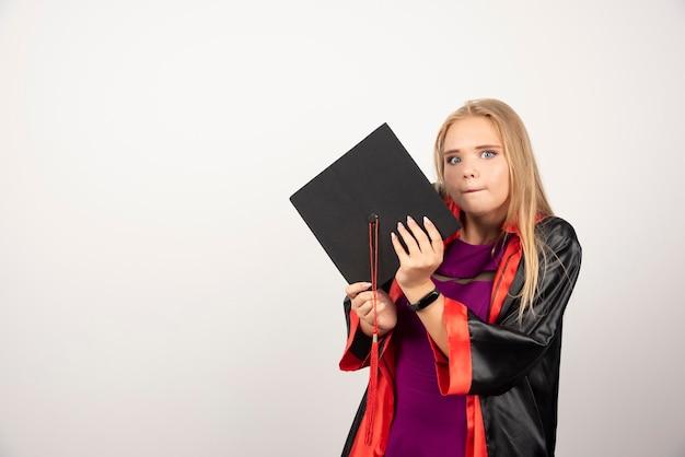 彼女を抱きしめて白を正面から見ている金髪の学生。