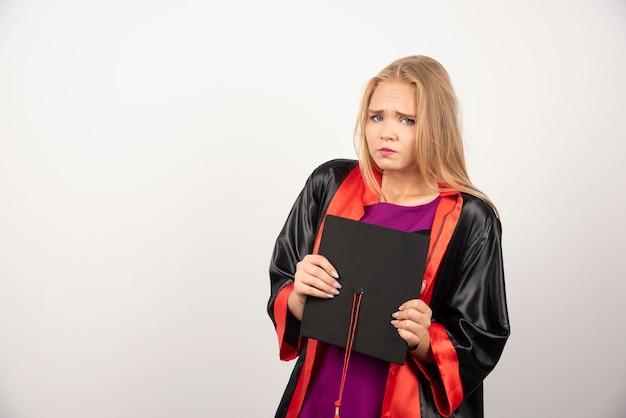 白で彼女の帽子を保持している金髪の学生。