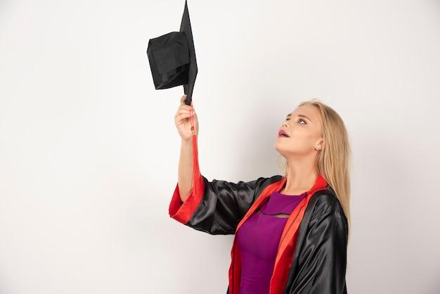 白で彼女の帽子を見ている金髪の学生。