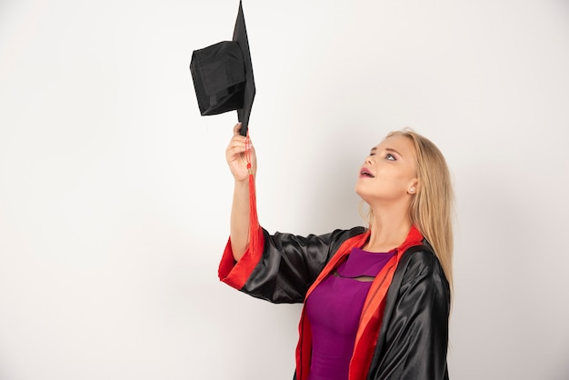 Blonde student looking at her cap on white.