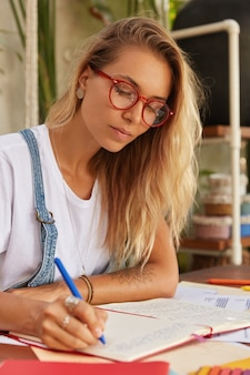 Blonde student in optical red rimed eyewear makes research for course paper