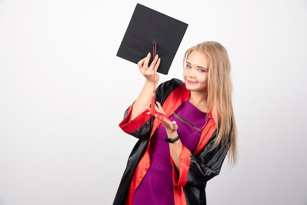 白い背景の上の彼女の帽子でポーズをとる金髪の学生。高品質の写真