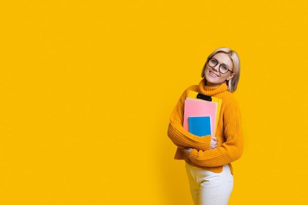 안경 앞에 미소를 짓고 여유 공간이있는 노란색 벽에 포즈를 취하는 동안 책을 들고있는 금발 학생