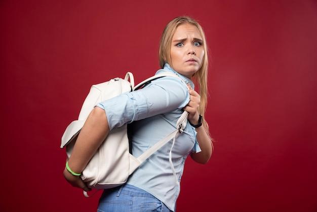 Donna bionda studentessa che porta uno zaino pesante.