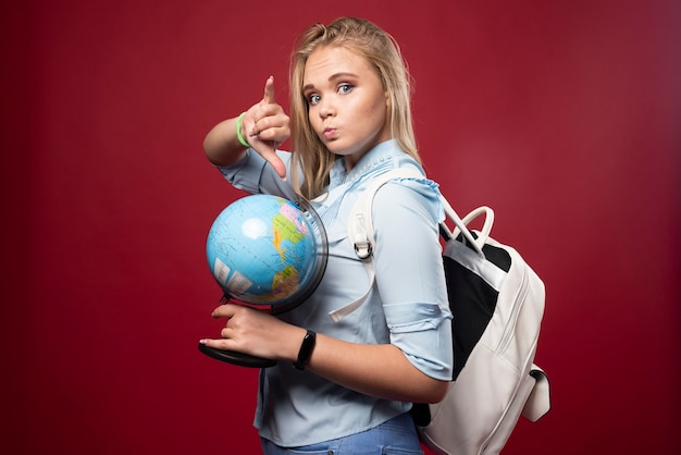 Blonde student woman holds a globe and pointing a place.