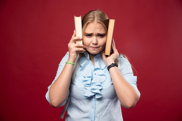 금발의 학생 여자는 책을 들고 귀를 덮습니다.