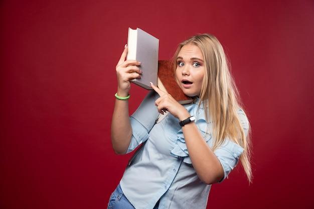 금발 학생 여자는 그녀의 책을 보유 하 고 행복을 느낍니다.