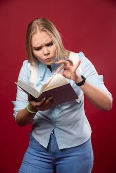 금발의 학생 여자는 그녀의 책을 들고 겁에 질린 것처럼 보입니다.