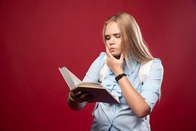 금발의 학생 여자는 책을 읽고 신중하게 생각합니다.