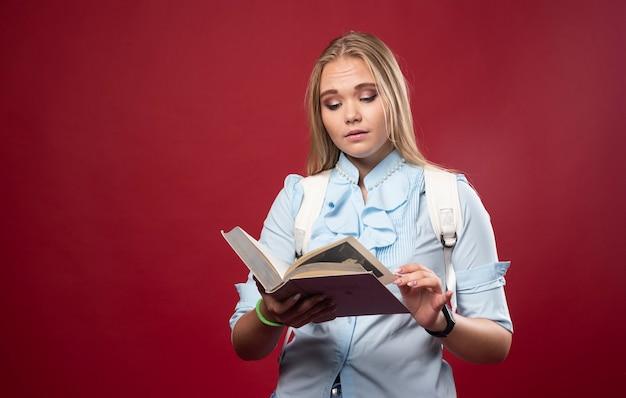 La studentessa bionda legge un libro e capisce.