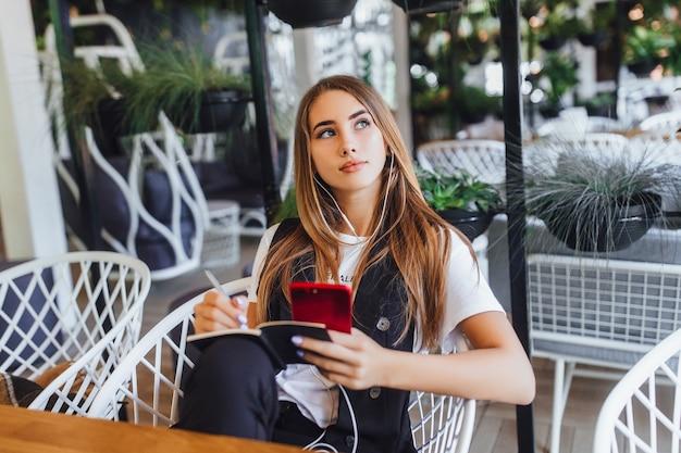 Успешная блондинка слушает музыку в кафе