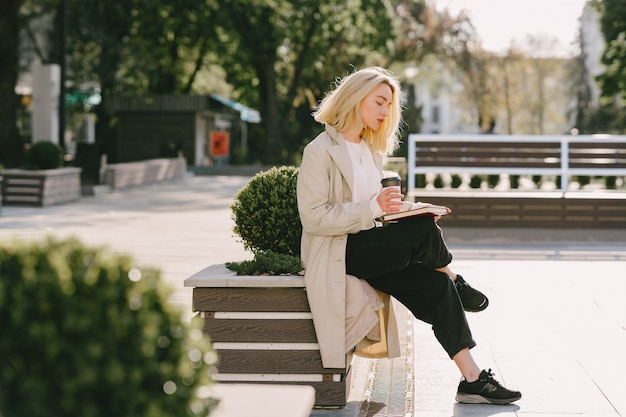 Blonde in a summer city with cup of coffee