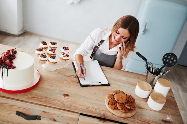 Блондинка принимает заказ по телефону. домашнее печенье и пирог на столе.