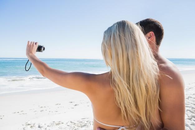 ボーイフレンドと自分自身の写真を撮っているブロンド