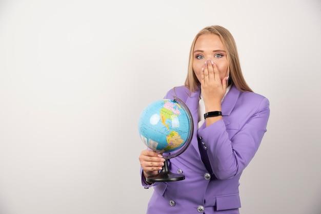 地球儀を持って彼女の口を覆っている金髪の先生。高品質の写真