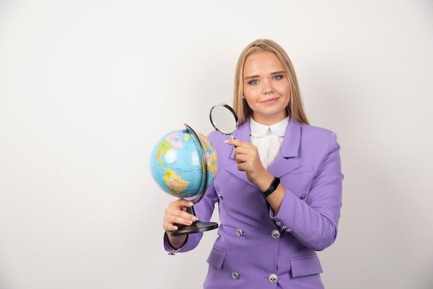 Блондинка учитель, глядя на глобус с увеличительным стеклом. фото высокого качества