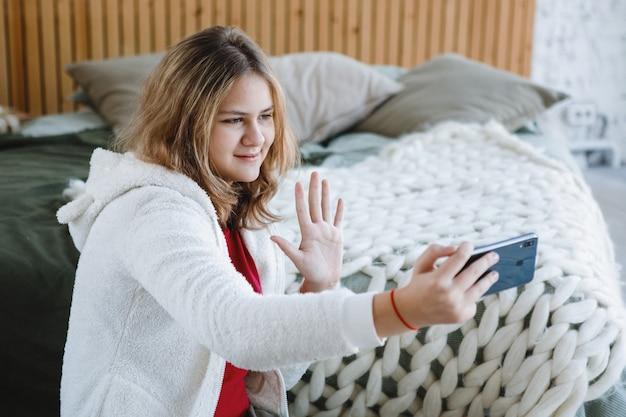 Блондинка со смартфоном сидит на полу возле дивана и делает селфи