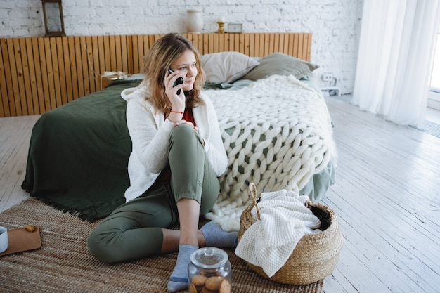 Блондинка со смартфоном сидит на полу возле дивана