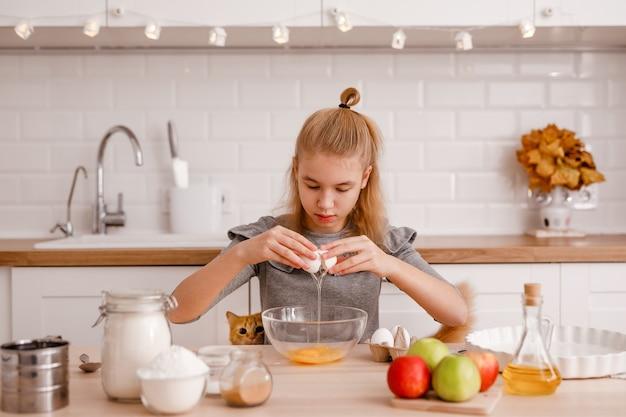 Блондинка в сером платье готовит традиционный яблочный пирог на новой кухне.