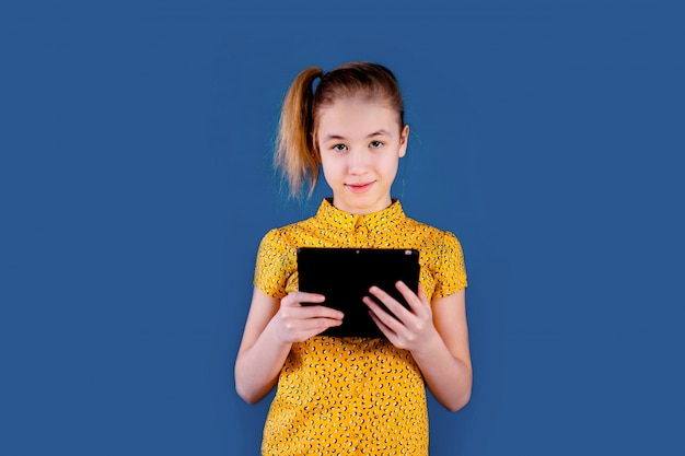 Blonde teenage girl playing with tablet  on blue wall. education concept