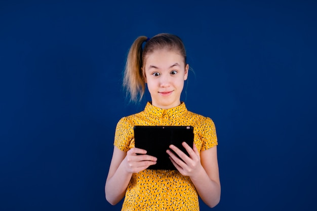 Blonde teenage girl playing with tablet pc on blue wall. education concept