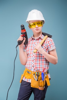 Blonde teenager blonde in the construction helmet with a screwdriver and hammer