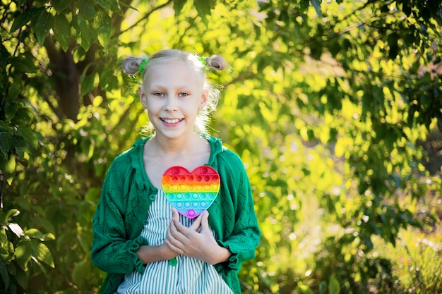 A blonde teenager girl sits in nature and plays a sensory toy in the form of a rainbow-colored heart.