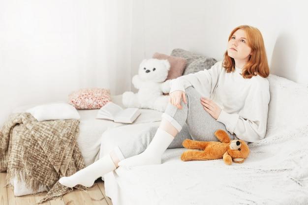 Белокурая девушка-подросток с мишкой на диване у себя дома