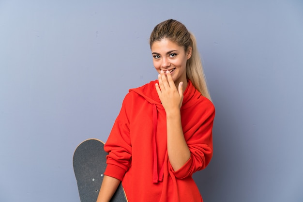 Blonde teenager skater girl over grey wall smiling a lot
