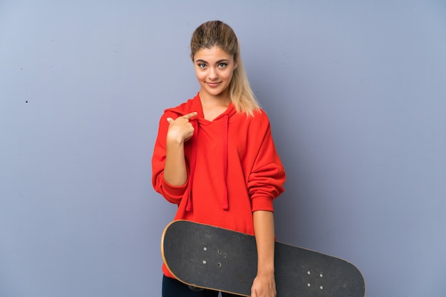 Blonde teenager skater girl over grey wall with surprise facial expression