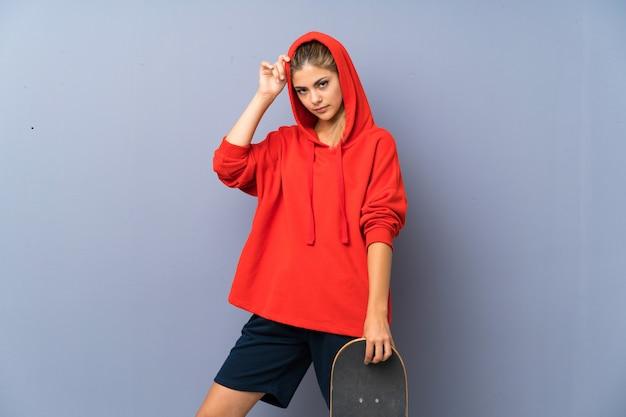 Blonde teenager skater girl over grey wall