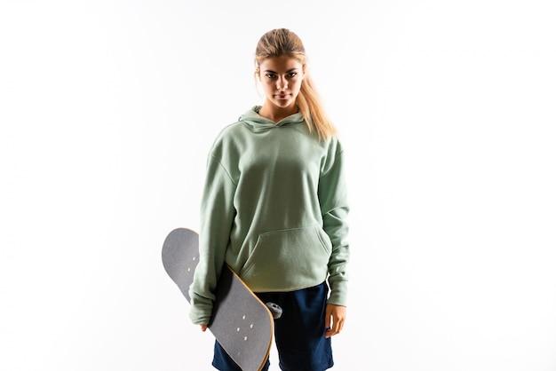 Blonde teenager skater girl over isolated white wall