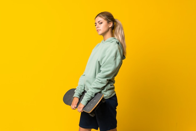 Blonde teenager skater girl over isolated yellow wall