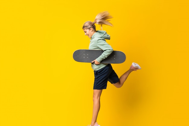 Blonde teenager skater girl jumping over isolated yellow background