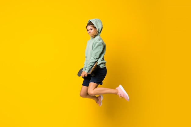 Blonde teenager skater girl jumping over isolated yellow